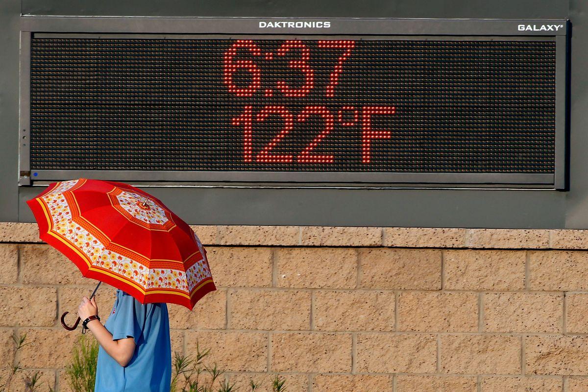 Una mujer pasa junto a un letrero que muestra la temperatura en Phoenix, Arizona.