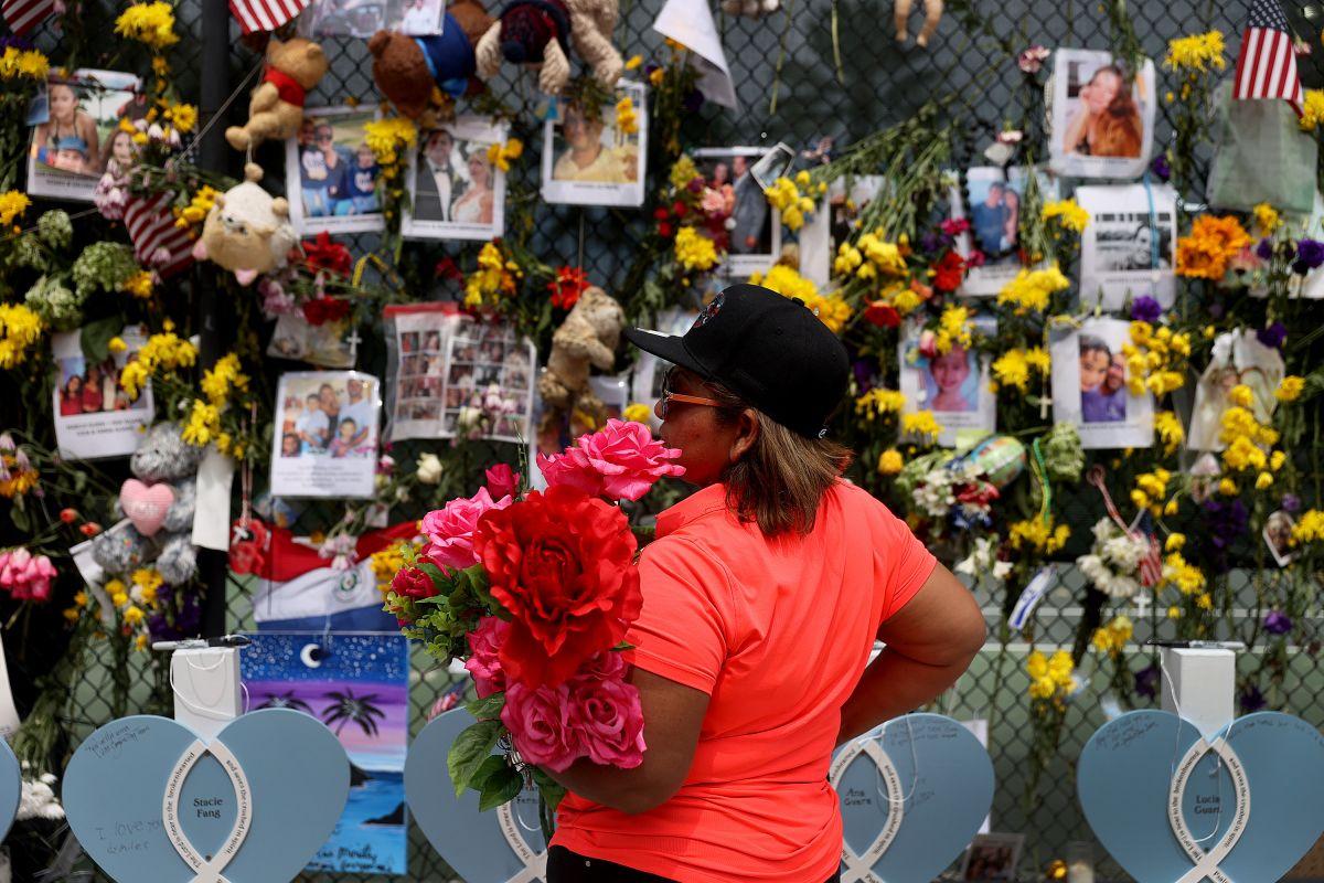 La gente visita el monumento con fotos de algunos de los desaparecidos de Champlain Towers South.