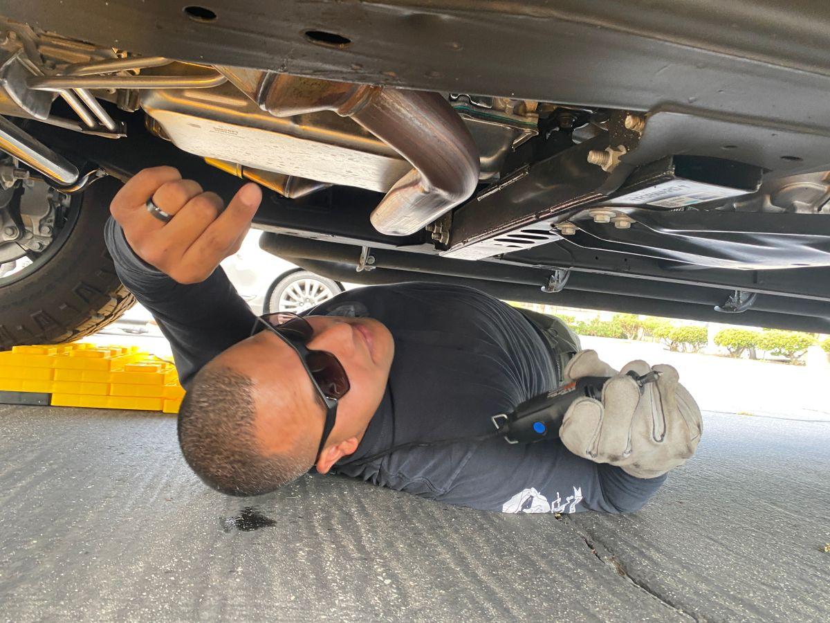 El agente del Sheriff Juan Cruz debajo de un auto mientras graba sobre un catalizador. / fotos: Jorge Luis Macías.