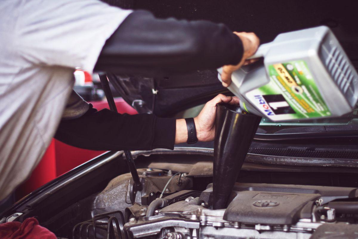 Foto de un hombre poniendo aceite de motor en un auto