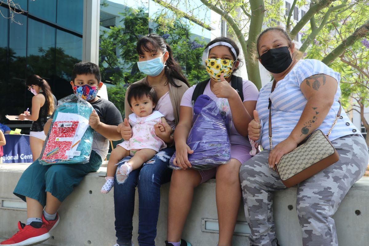 Los hijos de Verónica Jiménes (d), de 14, 11 y 6 años, recibieron ayer sus mochilas con útiles. / fotos: Jorge Luis Macías.