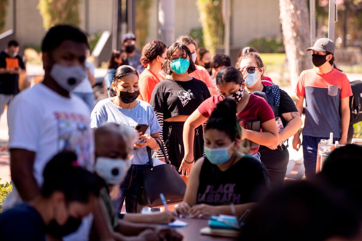 Personas en línea para vacunarse en una biblioteca pública en Los Ángeles.
