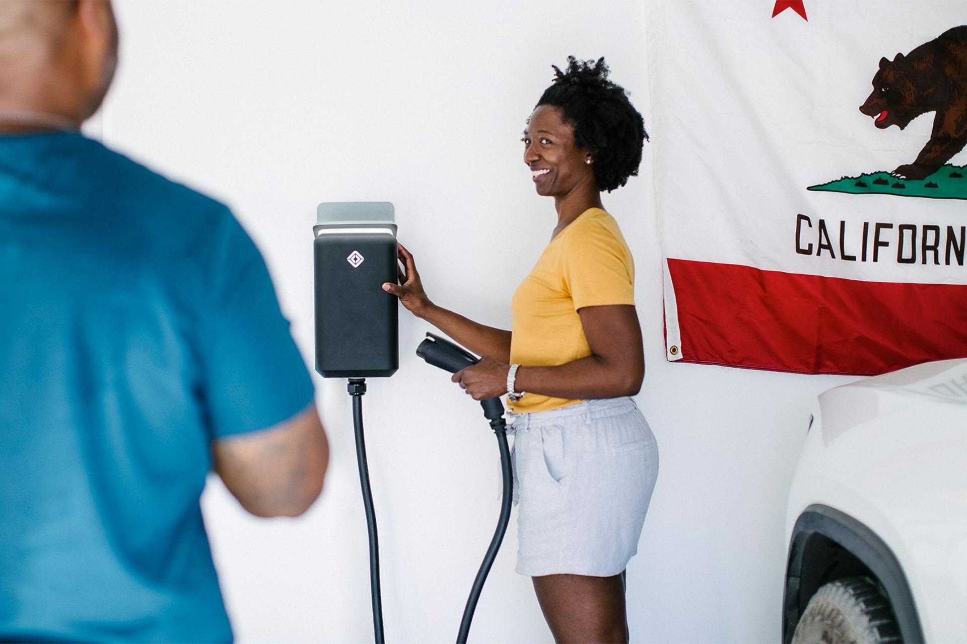 Foto de una mujer usando un cargador para vehículos eléctricos de Rivian.