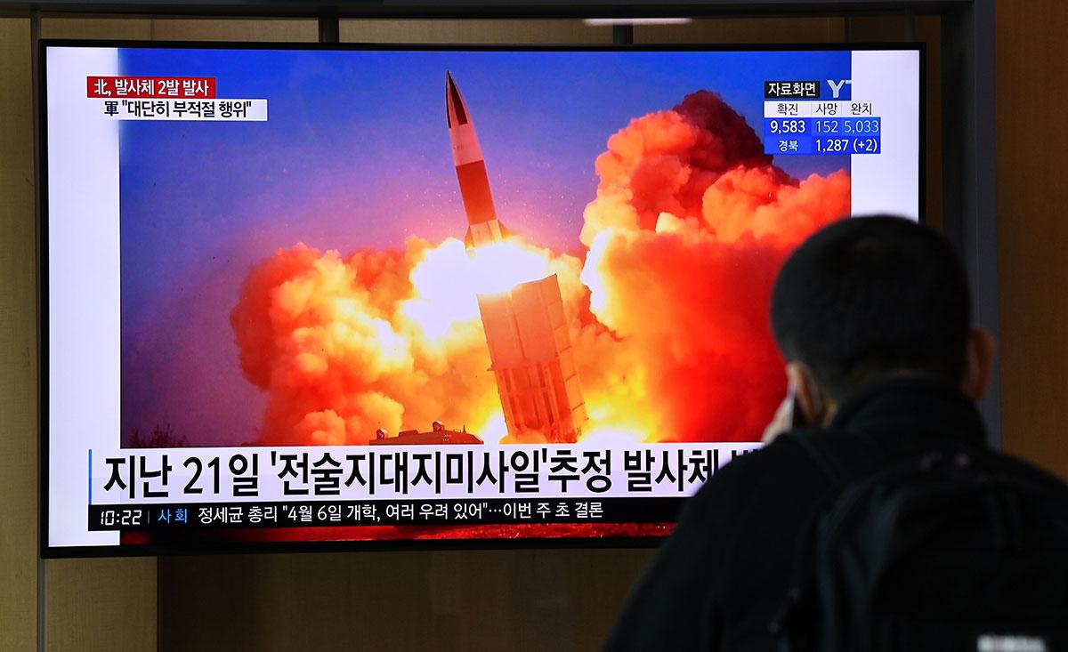 Un hombre mira una transmisión de prueba de misiles en Corea del Norte.