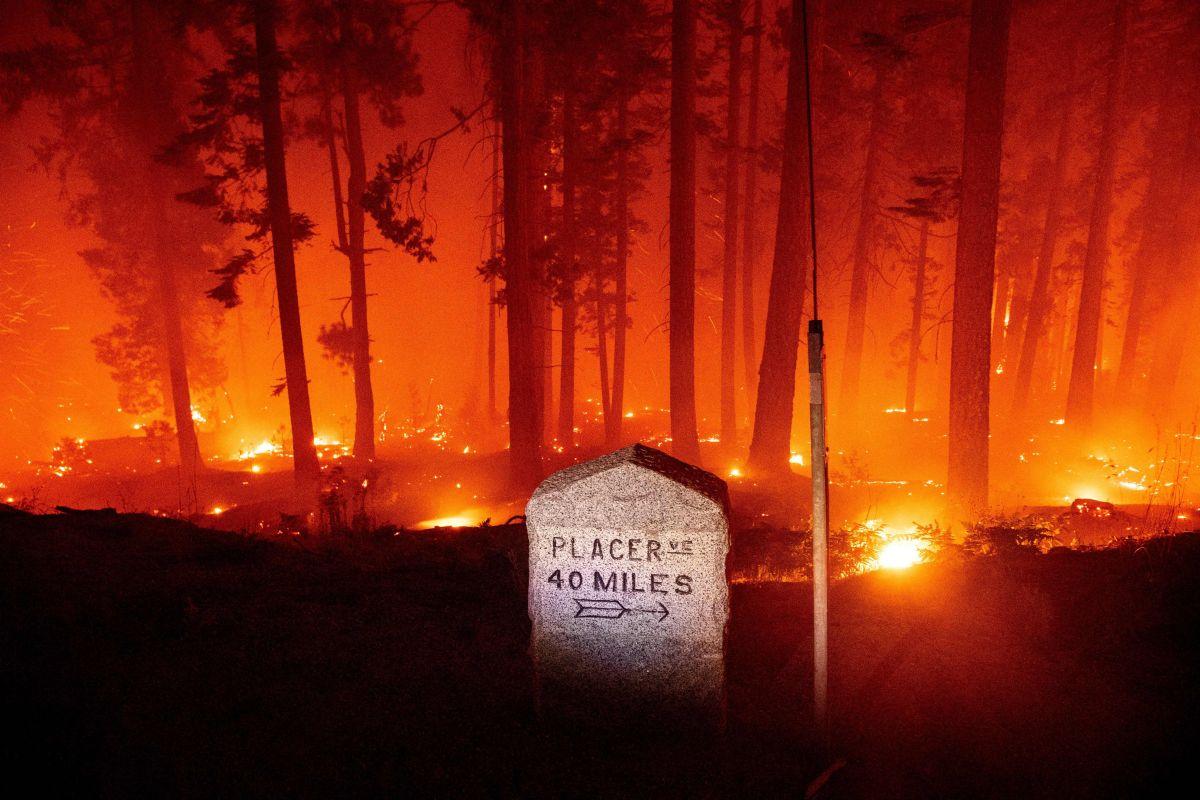 Un marcador de millas a Placerville rodeado de llamas durante el incendio Caldor, en California.