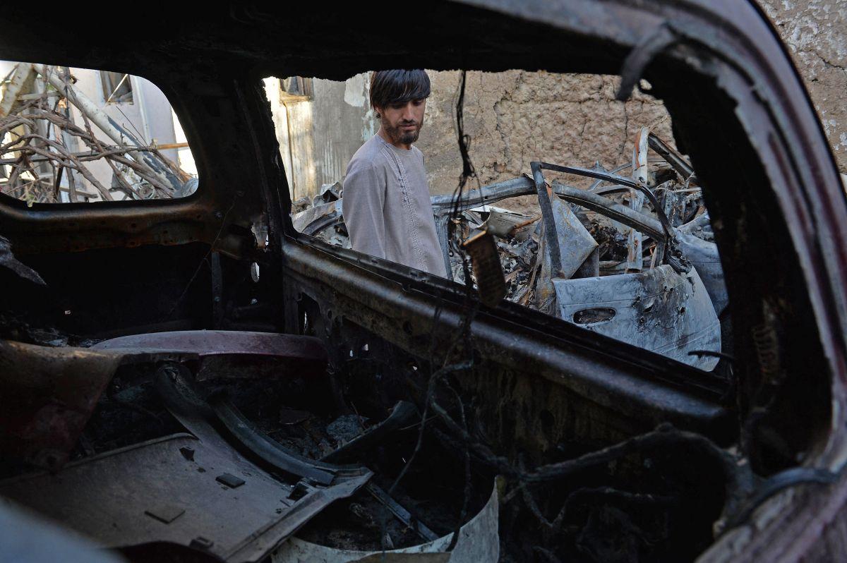 Un pariente de Ezmarai Ahmadi ante los restos del vehículo dañado en un ataque con aviones no tripulados de EE.UU.