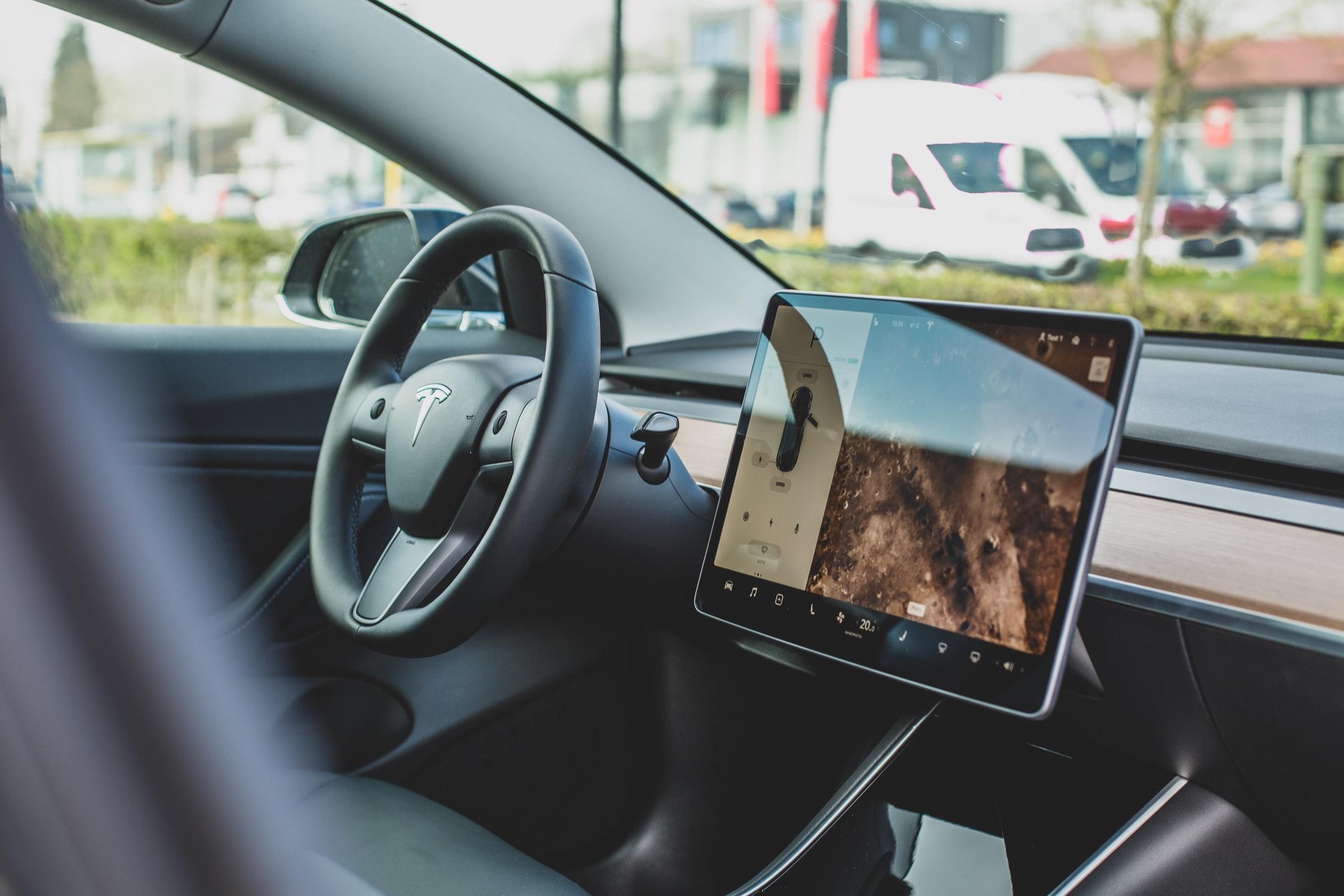 Foto del interior de un auto Tesla mostrando la pantalla y el volante