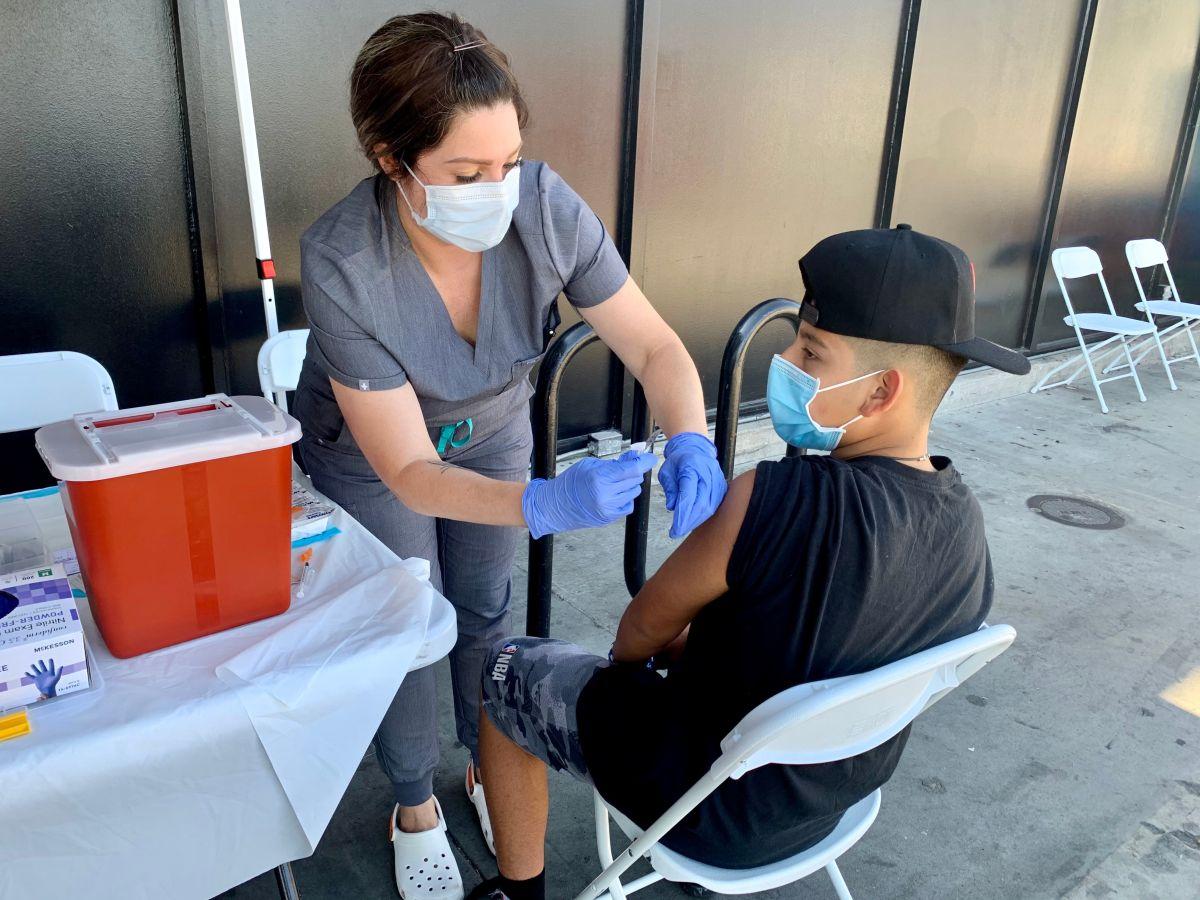 La enfermera Elisa Méndez aplica la vacuna contra covid a Derek León, un menor de 14 años. (Araceli Martínez/La Opinión)