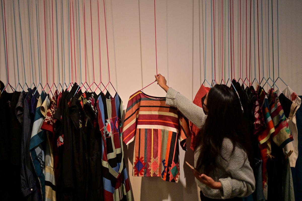 """Una mujer trabaja en una tienda de prendas confeccionadas con telas creadas en las comunidades indígenas mexicanas de la empresa """"Fabrica Social""""."""