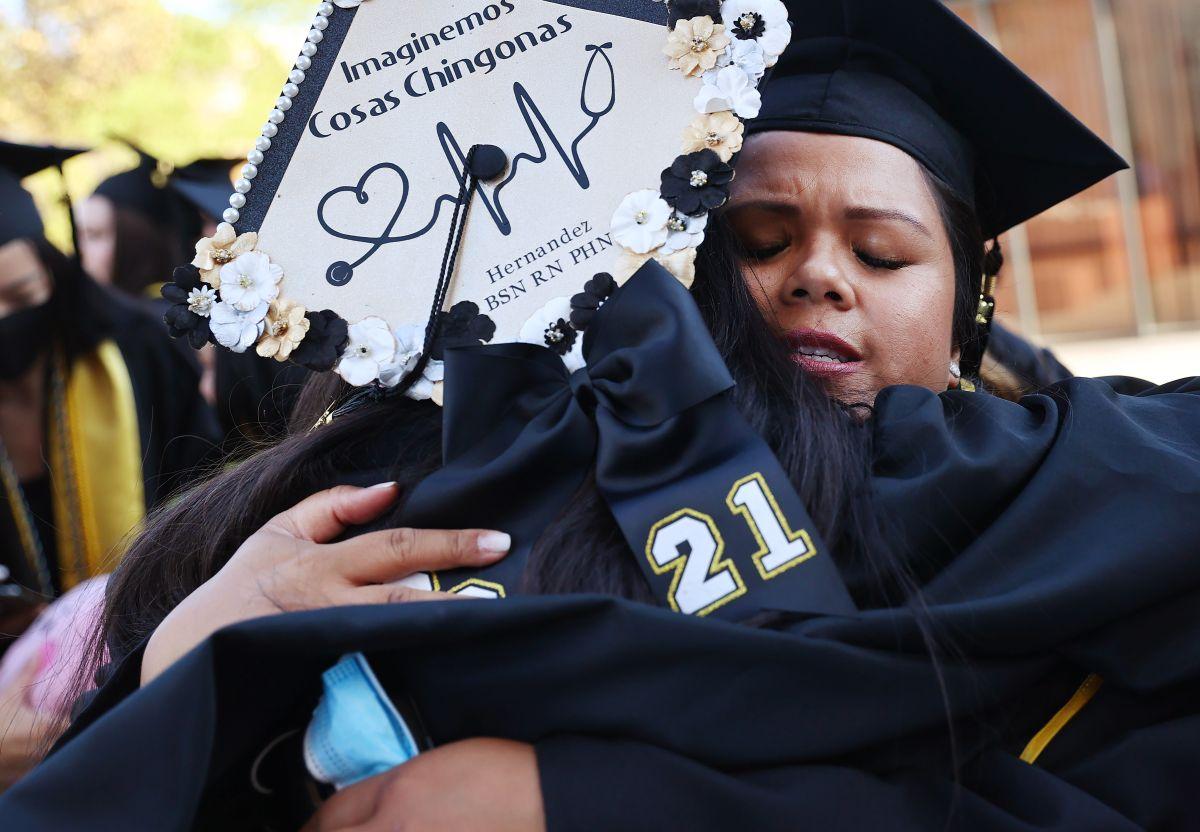 LOS ÁNGELES, CALIFORNIA - 27 DE JULIO: La graduada de Cal State Los Ángeles, Maricris Trask (R), quien es madre y veterana de la Marina de los EE. UU., Abraza a otro graduado luego de su ceremonia de graduación que se llevó a cabo al aire libre debajo de una carpa en el campus el 27 de julio de 2021 en Los Angeles, California.